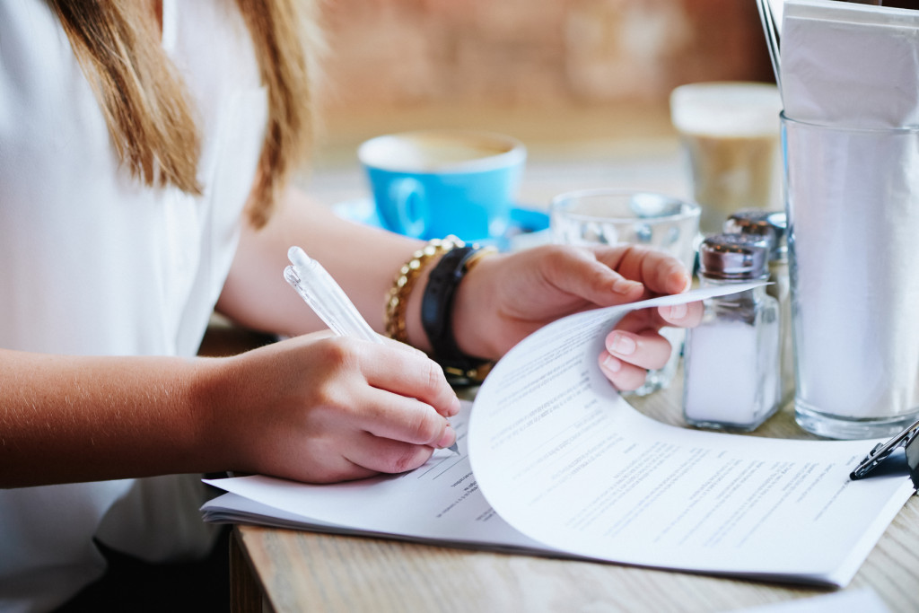 Client reading and signing legal document at a meeting in a cafe